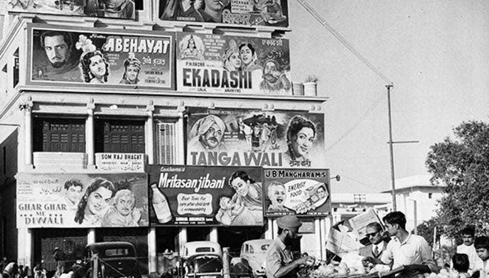 A man buys fruit in front of a hoarding promoting several films in Delhi in 1950.