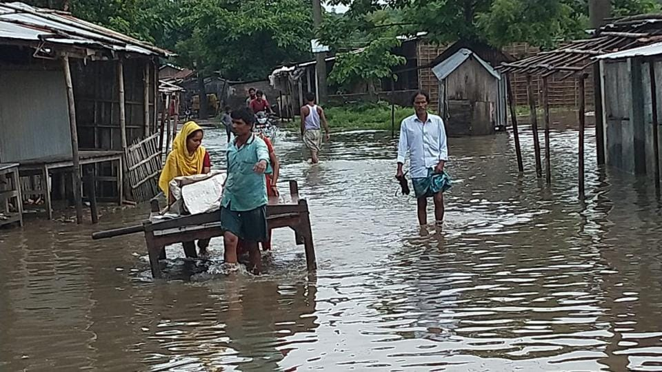 People struggle to move on a street flooded with water in Bihar. (HT Photo)