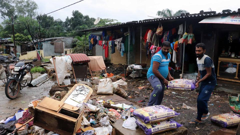 Shop owners from Sonivali village throw away sacks of rice, which was destroyed after the flood water entered their premises in Badlapur.