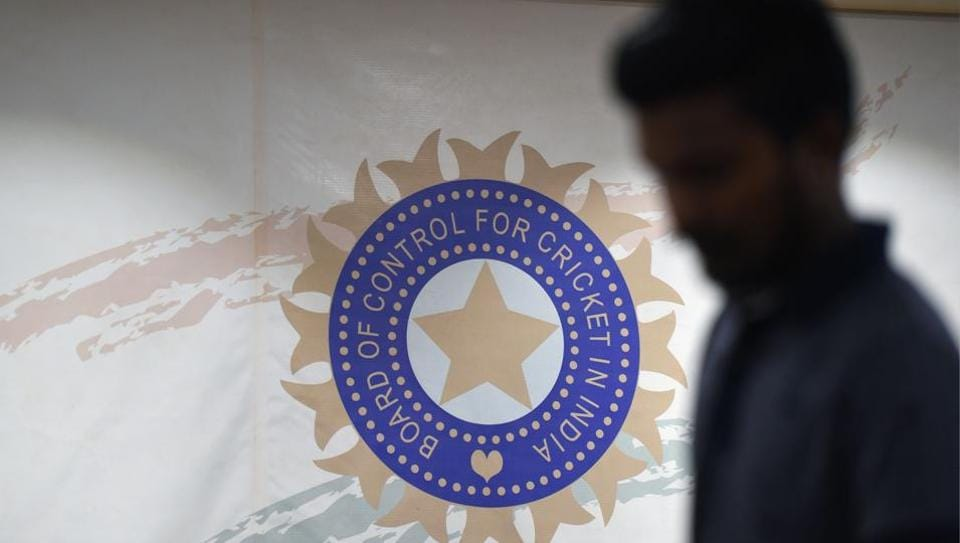 A man walks in front of the logo for the Board of Control for Cricket in India (BCCI)