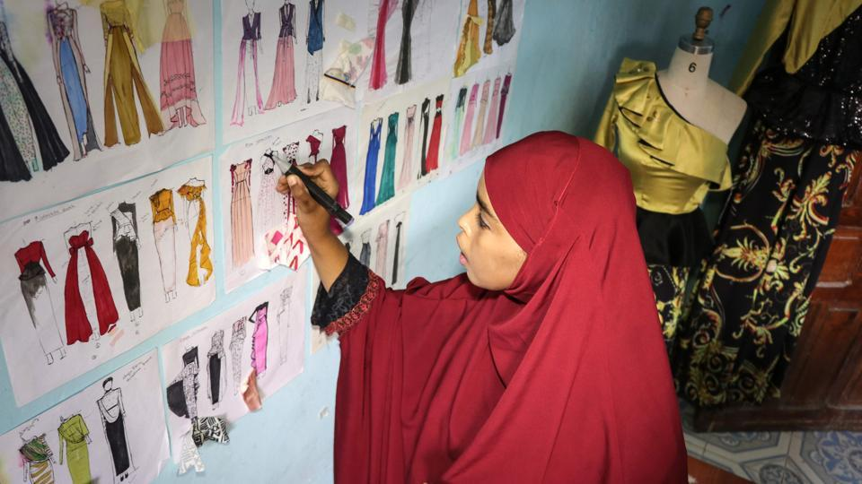 (FILES) In this file photo taken on November 4, 2018 Muna Mohamed Abdullahi, 24 year-old, owner of Mkena Designs, draws her new creations on a wall at her home in Modadishu, Somalia. (Photo by Abdi HAJJI HUSSEIN / AFP)