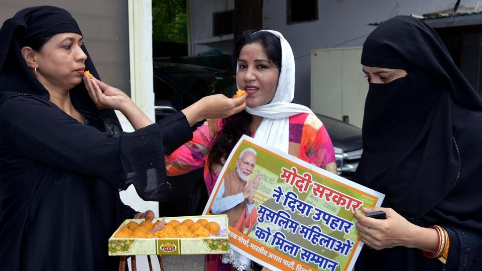 Muslim women offer sweets to each other as they celebrate the passage of triple talaq bill at Delhi BJP Office in New Delhi .