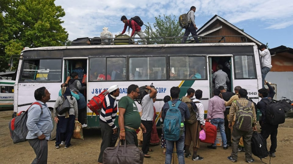Tourists  walk towards their bus in Srinagar to leave Kashmir valley after a government advisory about a terror threat.