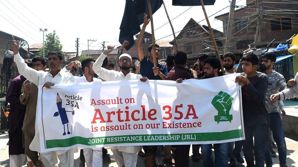 """Kashmiri muslims shout anti-Indian slogans during a demonstration against attempts by the NGO 'We the Citizens' and individual citizens to revoke article 35A and 370, in downtown Srinagar on August 3, 2018. The articles empower the Jammu and Kashmir state legislature to define permanent residents of the state and provide special rights and privileges to those permanent residents in Jammu and Kashmir.Mirwaiz warned that """"a mass agitation of hitting and occupying streets will be launched if any tinkering with Article 35-A is allowed to take place. / AFP PHOTO / Tauseef MUSTAFA"""