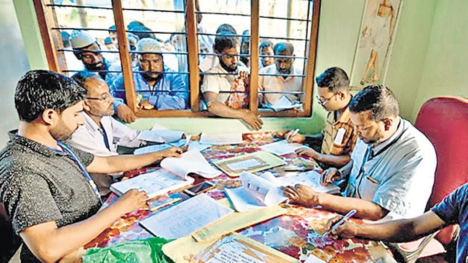 People wait to check their names on the draft list at the National Register of Citizens (NRC) centre at a village in Nagaon district.