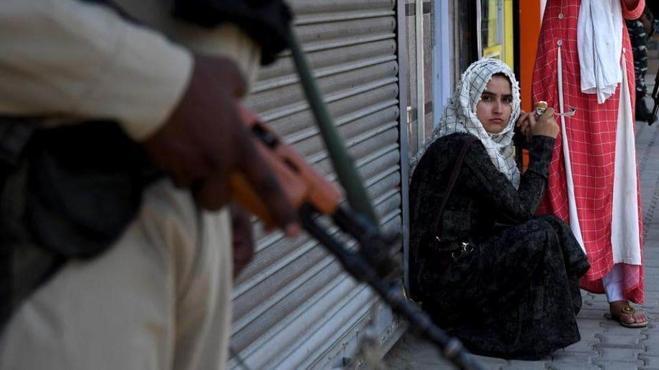 A woman sits as CRPF personnel stand guard in Srinagar.