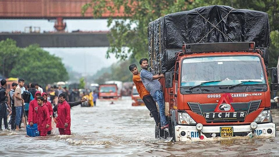 People walk from flooded road as there is water logging due to heavy rain on LBS Road near Sion station in Mumbai, on Sunday, August 4, 2019. (Photo by Pratik Chorge/Hindustan Times)