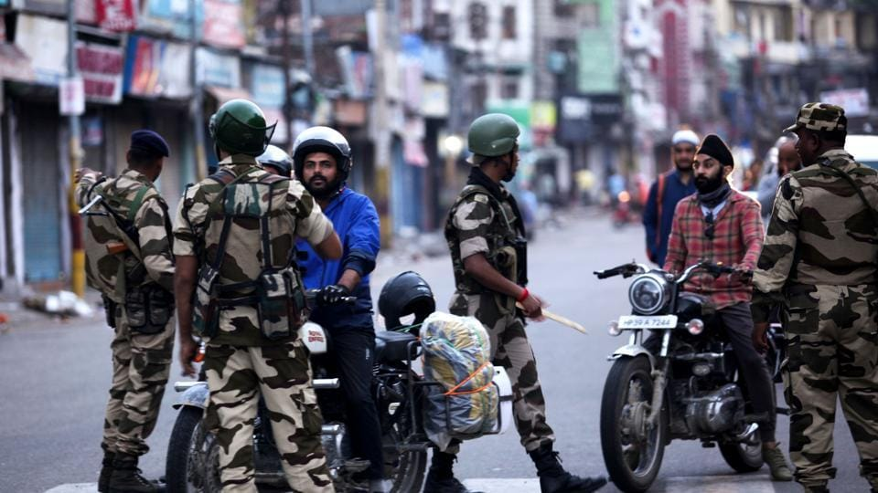 Security personnel question motorists on a street in Jammu on August 5, 2019.