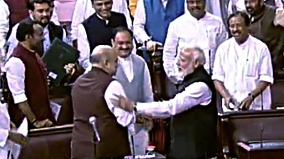 Prime Minister Narendra Modi greets Union Home Minister Amit Shah after the Jammu and Kashmir Reorganisation Bill being passed by Rajya Sabha.
