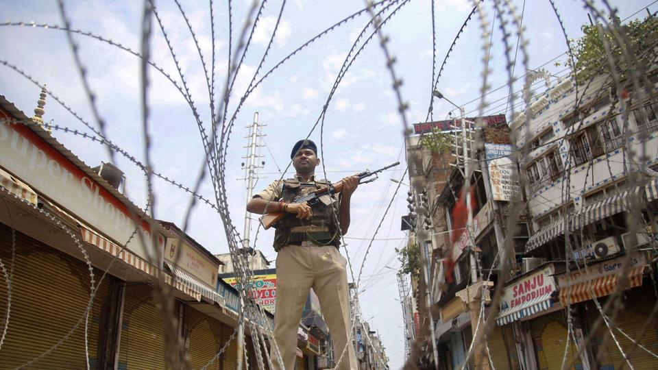 CRPF personnel stand guard during restrictions, at Raghunath Bazar in Jammu, Monday, Aug 05, 2019. Restrictions and night curfews were imposed in several districts of Jammu and Kashmir as the Valley remained on edge with authorities stepping up security deployment.