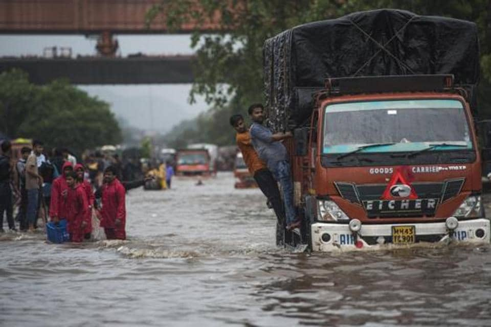 Mumbai, India - Aug. 4, 2019: People walk from flooded road as there is water logging due to heavy rain on LBS Road near Sion station in Mumbai, India, on Sunday, August 4, 2019. (Photo by Pratik Chorge/Hindustan Times)