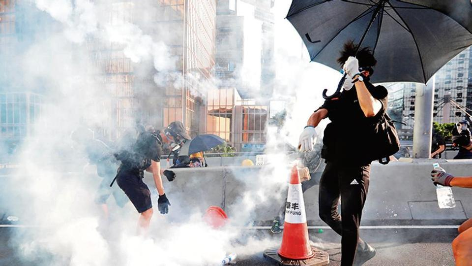 Protesters react after tear gas was fired by the police during a demonstration in support of the city-wide strike and to call for democratic reforms outside Central Government Complex in Hong Kong, China, August 5, 2019.