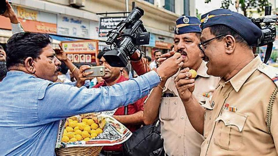 Shiv Sena workers offer sweets to policemen as they celebrate the effective revoking of Article 370 in Mumbai.