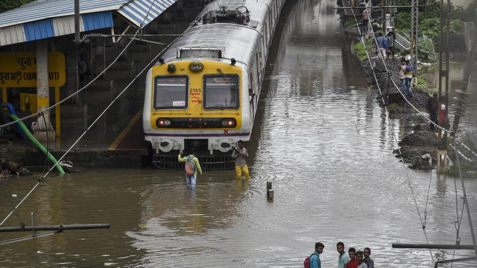 People walk on water logging track at Chunabhati railway station in Mumbai. Central Railway (CR) cancelled 23 outstation trains on Monday, including Deccan Queen and Pragati Express.