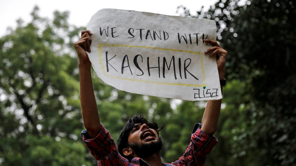 A man holds a sign and shouts slogans during a protest after the government scrapped the special status for Kashmir, in New Delhi, India, August 5, 2019.