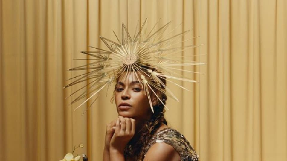 The singer is seen in a shimmery gold Valentino dress and a hat by Philip Treacy London.