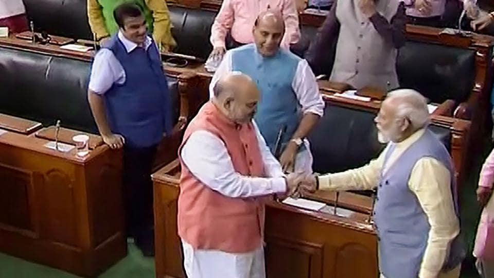Prime Minister Narendra Modi shakes hands with Union Home Minister Amit Shah after Parliament approved the abrogation of special status given to J&K under Article 370, in the Lok Sabha, in New Delhi, Tuesday, Aug 6, 2019.