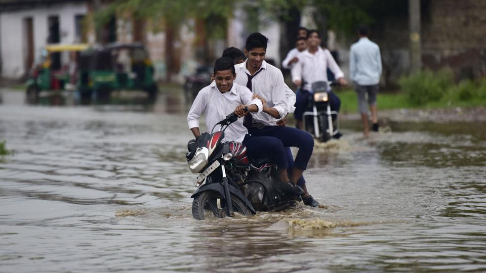 School boys ride a motorcycle through a waterlogged road after heavy rain at Dhanauri in Greater Noida, on Tuesday, August 6, 2019.