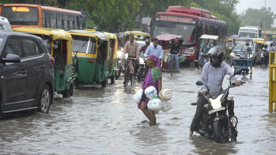 Vehicles wade through a waterlogged road after heavy rain, near Patparganj, in New Delhi, on Tuesday, August 6, 2019.
