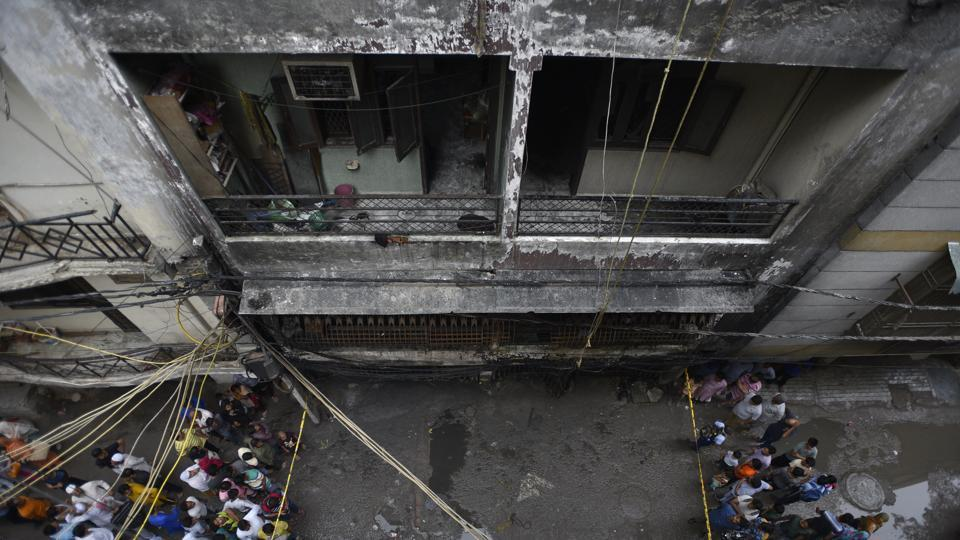 People gathered around the location of a fire that broke out in a multi-storey building in Okhla's Zakir Nagar in the early hours of the day.