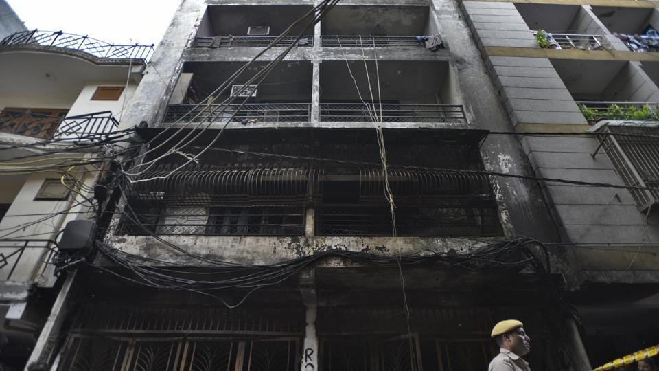 People and police personnel gathered around the building in south Delhi's Zakir Nagar where a fire broke out in the early hours of  Tuesday, August 6, 2019.