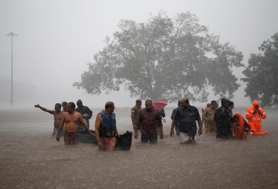 Kerala rain: Members of a rescue team wade through a water-logged area during heavy rains on the outskirts of Kochi