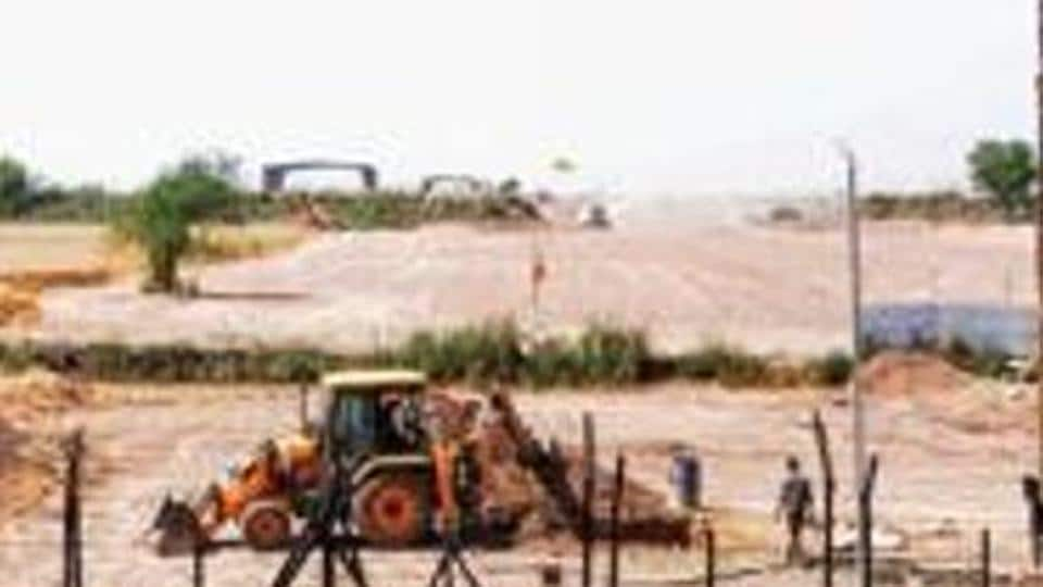 Heavy machines at work beyond the border fence for the construction of the Indian side of Kartarpur