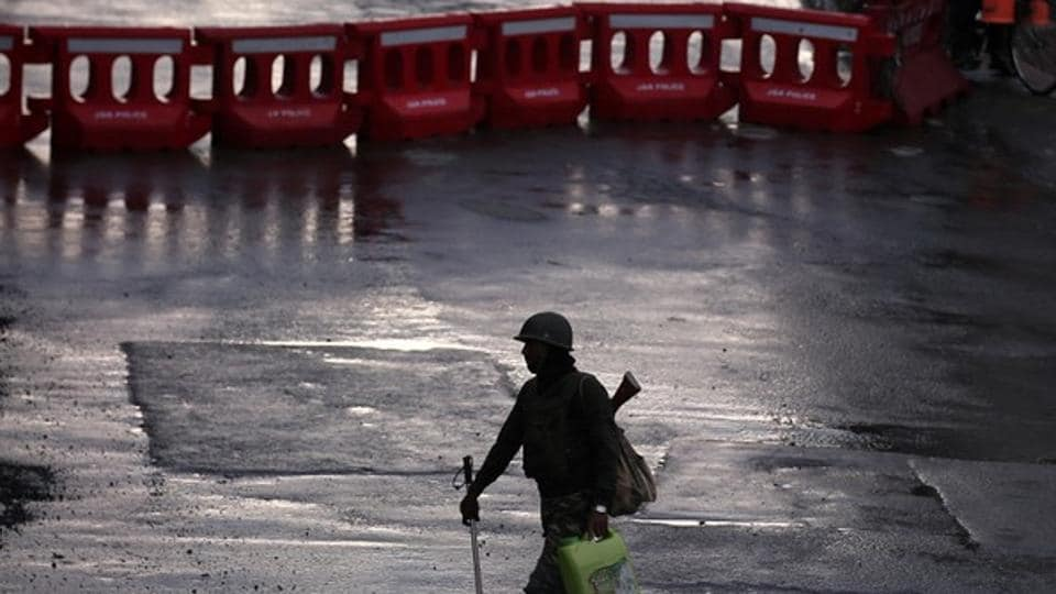 A security force personnel patrols a deserted road during restrictions in Srinagar.