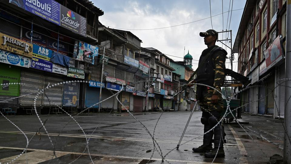 Security personnel stands guard on a street during a curfew in Srinagar on Thursday.