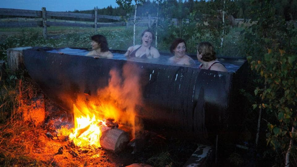 Latvian women bath in a huge tub heated by a bonfire. Almost every family owns the traditional Latvian dress, which they bring out for special occasions when songs and dances from the homeland are also performed. (Alexei Malgavko / AFP)