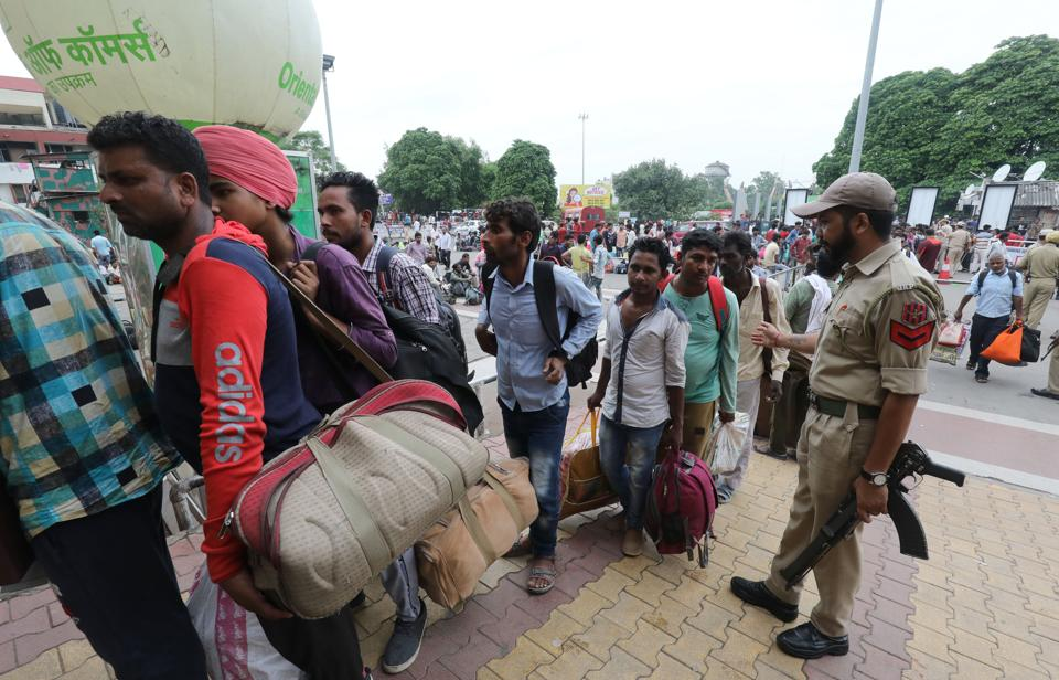 Migrant labourers who were working in Kashmir valley, flee from Kashmir as they arrive at the railway station to board a train to leave for their homes, in Jammu .