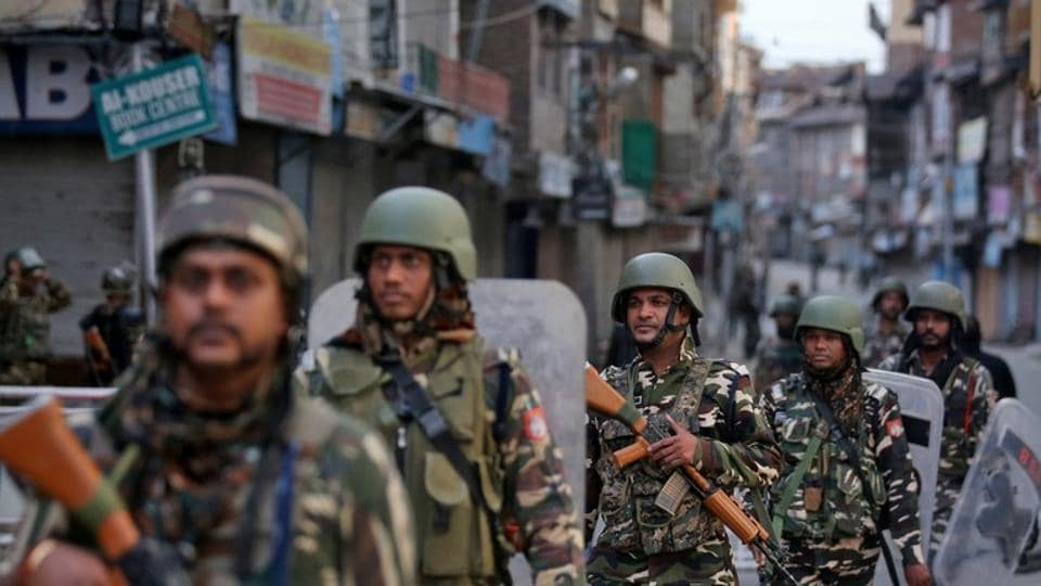 Security forces personnel patrol a deserted street during restrictions in Srinagar