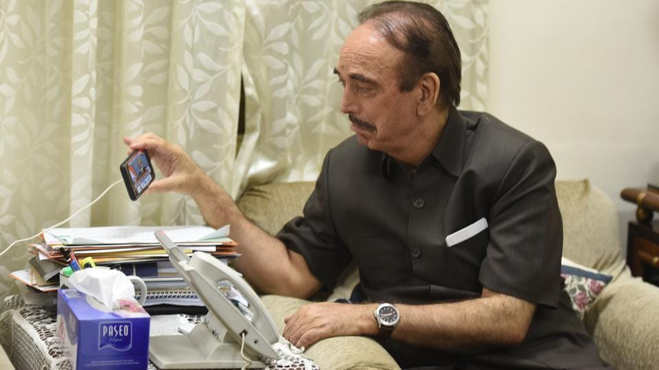 Senior Congress leader Ghulam Nabi Azad watching Prime Minister Narendra Modi's address on a journalist's phone, in New Delhi. Azad was stopped at the Srinagar International airport on Thursday morning and sent back to Delhi by the local administration. He was accompanied by state Congress chief GA Mir. (Raj K Raj / HT Photo)