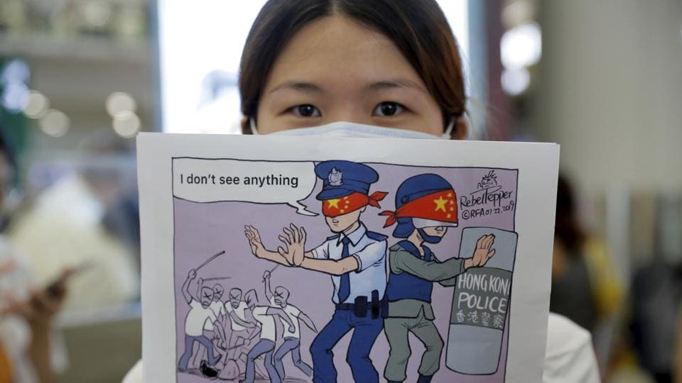 A woman holds up a cartoon depicting police feigning ignorance of thugs attacking protesters as she joins protesters during a second day of sit-in protest at the airport in Hong Kong.