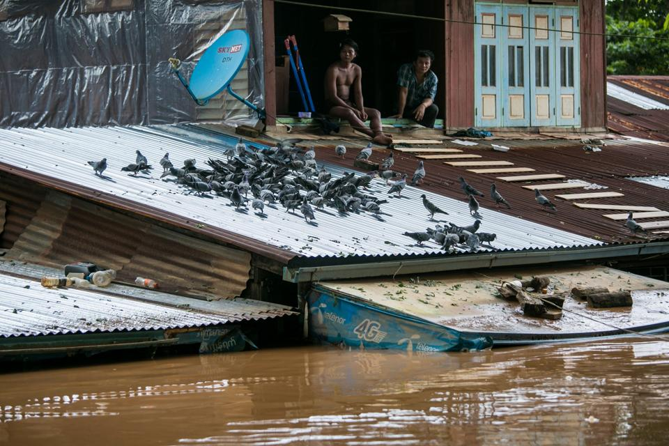 Residents look out from a window as floodwaters submerged areas of Ye township in Mon State. Myanmar troops and emergency responders scrambled to provide aid in flood-hit parts of the country Sunday after rising waters forced residents to flee by boat and a landslide killed at least 52 people. (Sai Aung Main / AFP)