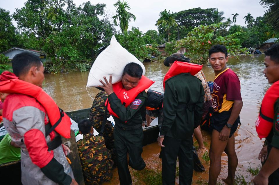 Army soldiers unload a sack from a boat. As the rainy season reaches its peak, the country's armed forces are pitching in and have readied helicopters to deliver supplies. (Sai Aung Main / AFP)