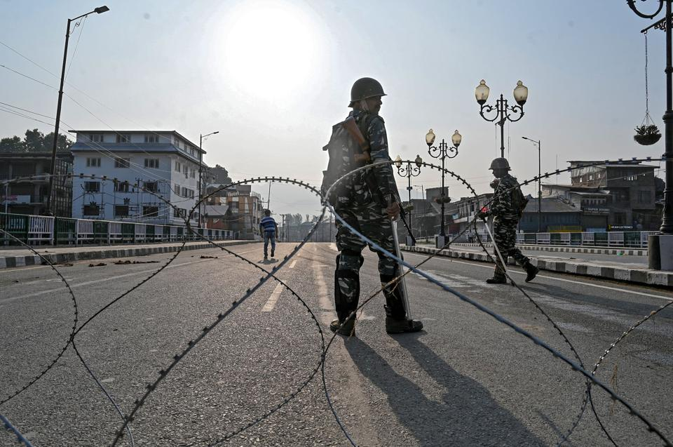 Paramilitary troopers stand guard behind a barbed fence wire as they block a road during a curfew in Srinagar. The Union Government moved a resolution in Rajya Sabha to scrap Article 370 of the Constitution that gives special status to Jammu and Kashmir. He also added that revocation of Article 370 will kickstart the development of Kashmir. (TAUSEEF MUSTAFA / AFP)