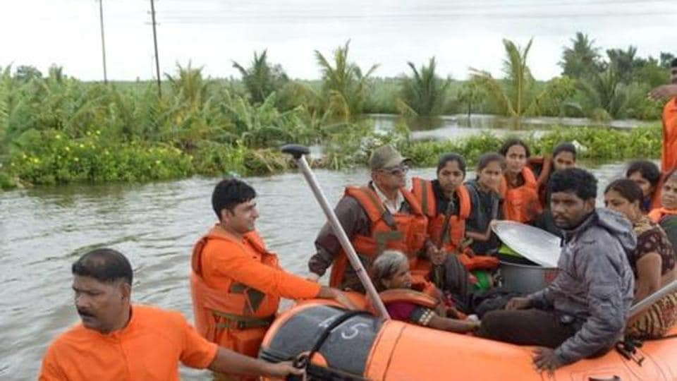 Members of National Disaster Response Force (NDRF) evacuate flood-affected people to a safer place in Sangliwadi, Sangli district, in Maharashtra.