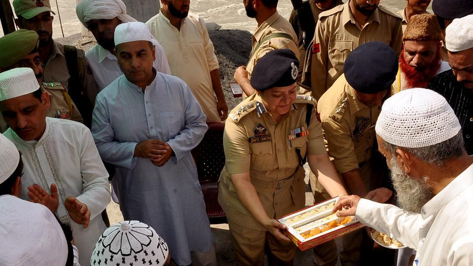 Police personnel offer sweets during the festival of Eid ul-Adha in Jammu on Monday. (ANI Photo)