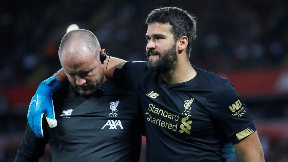 Liverpool's Alisson is helped off the pitch as he is substituted after sustaining an injury.