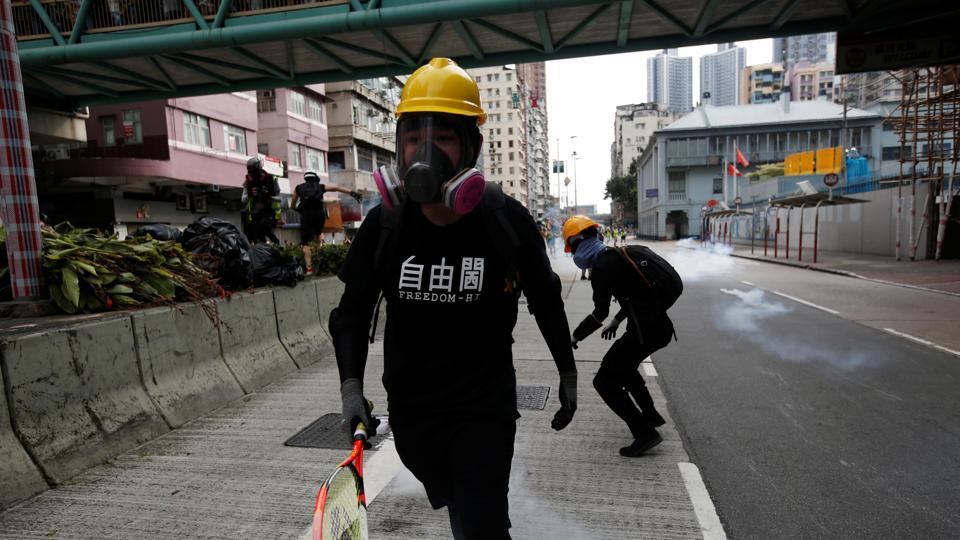 A protester in a Freedom-Hi T-shirt moves away from tear gas fired by police officers near Sham Shui Po police station in Hong Kong, China, August 11, 2019.