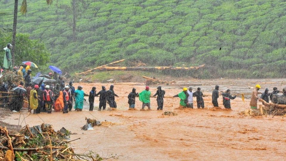 Rescuers help people to cross a flooded area after a landslide caused by torrential monsoon rains in Meppadi in Wayanad district. Over 2.5 lakh people across 14 districts were affected from heavy downpour while 32 people sustained injuries due to flood-related incidents. (REUTERS)