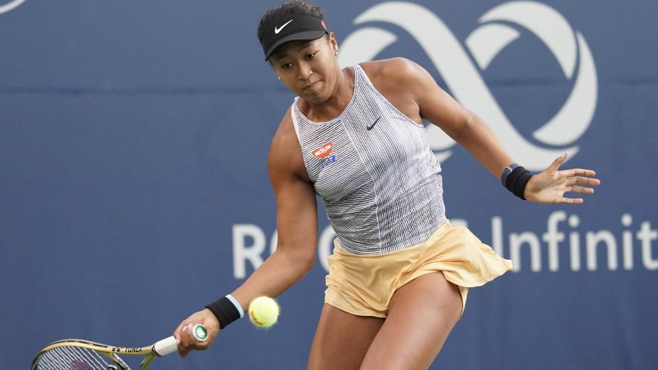 Naomi Osaka hits a ball to Serena Williams during the Rogers Cup tennis tournament.