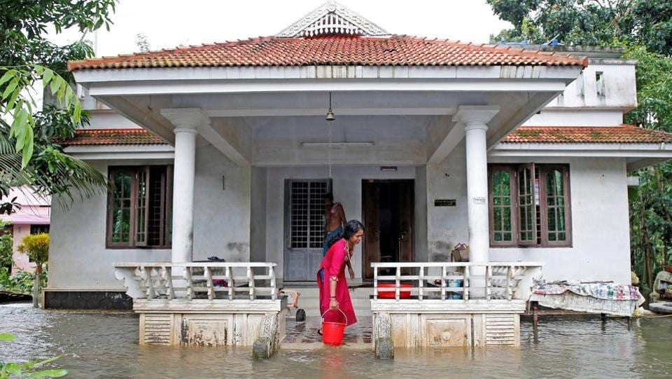 A woman clears out the water from her flooded house at Paravur on the outskirts of Kochi. Operations at the Cochin International Airport resumed on Sunday after a two-day break following the inundation of the runway area due to water from the nearby Periyar river entering the premises. (Sivaram V / REUTERS)