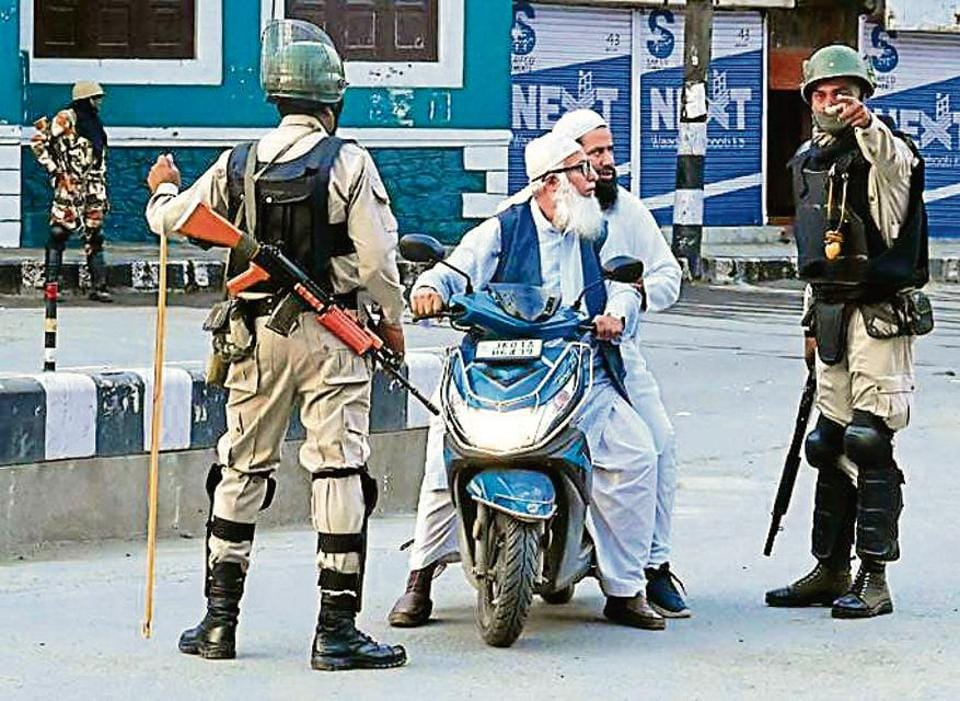 Security personnel stop Muslims for questioning during a lockdown in Srinagar on August 12, 2019.
