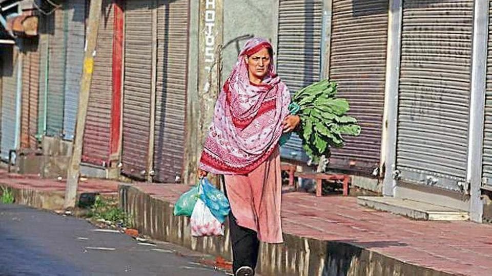 A woman carrying eatables walks past closed shops during restrictions after the government scrapped special status for Kashmir, in Srinagar.