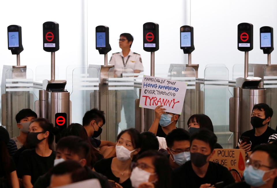 Anti-government protesters sit on the floor in front of security gates during a demonstration at Hong Kong Airport, China August 13, 2019.