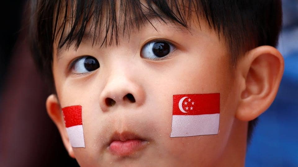 A young boy, face painted with national flag is seen during Singapore's 54th National Day Parade in Singapore. The Monetary Authority of Singapore is likely to ease policy when it reviews its stance in October, economists say.