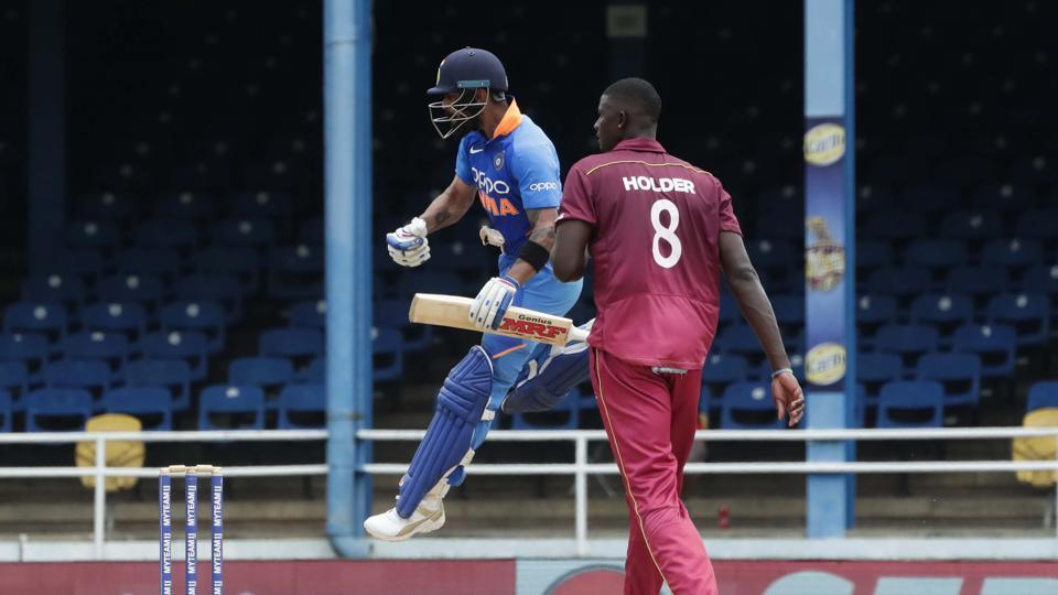 India's captain Virat Kohli celebrating his century as West Indies bowler captain Jason Holder looks on during their second One-Day International.