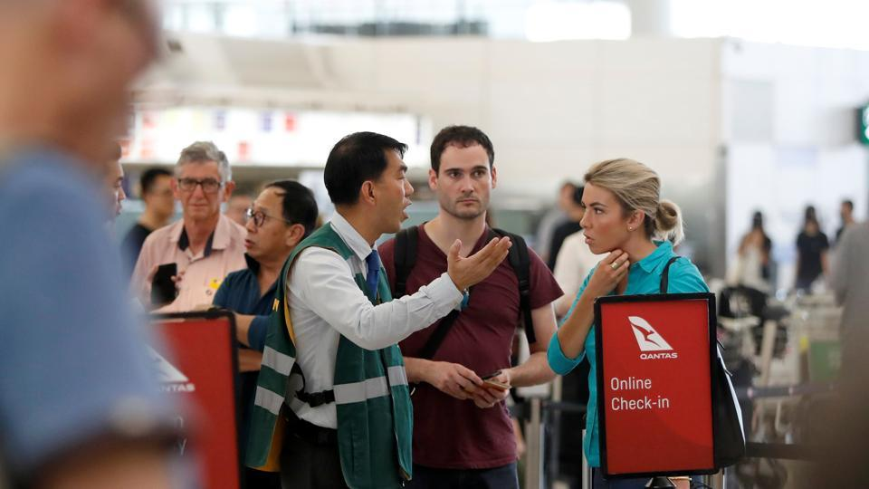Passengers talk with a member of the airport staff after the announcement that all airport operations are suspended due to an anti-government demonstration at Hong Kong Airport, China August 13, 2019.